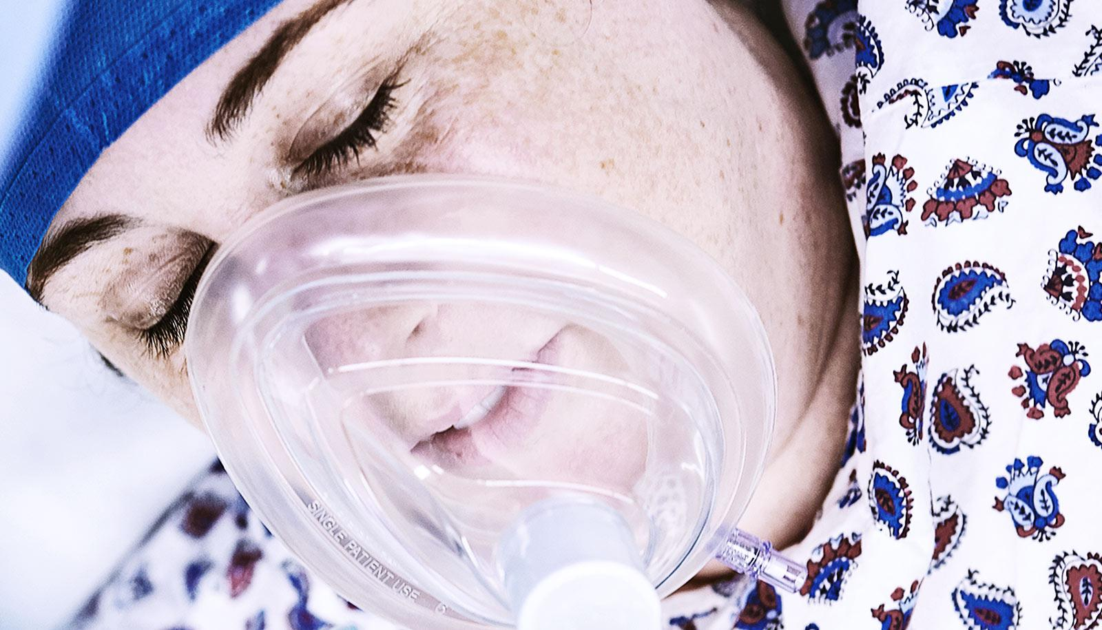 A woman in a hospital gown and with an anesthesia mask on is unconscious.