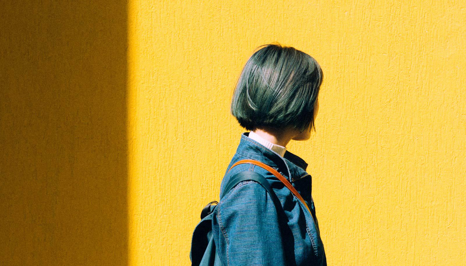 woman looks away walking in front of yellow wall