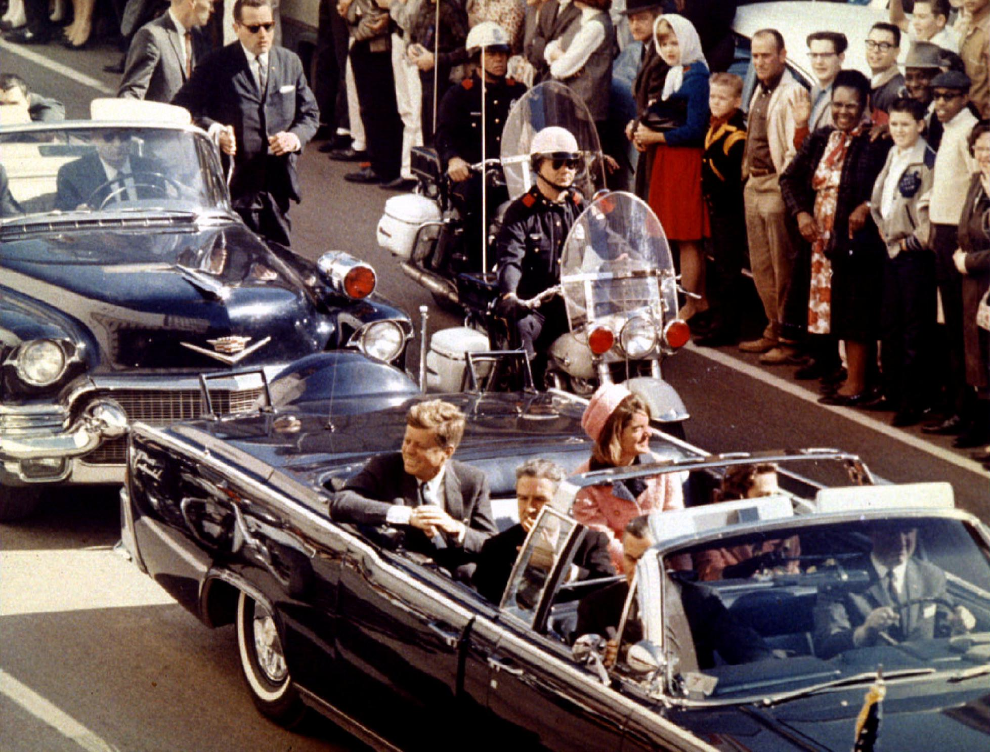 President John F. Kennedy, First Lady Jacqueline Kennedy and Texas Governor John Connally ride through Dallas moments before Kennedy was assassinated on November 22, 1963.