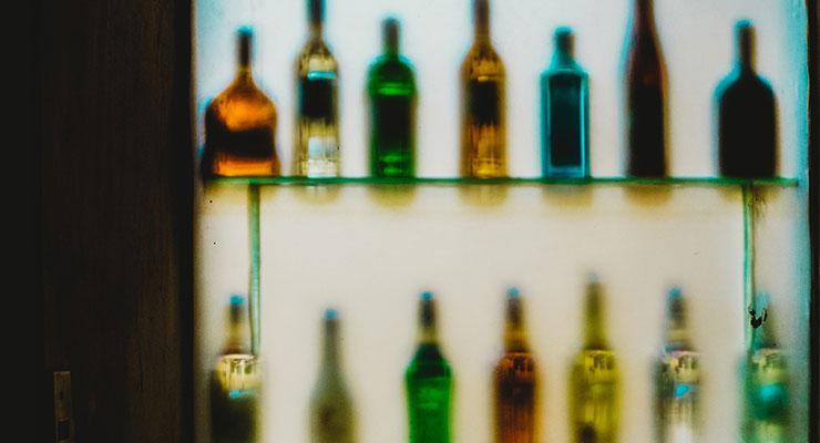 Recovering From Alcoholism: Admitting I Have a Problem Was the Hardest Part by Gordon Goad. Photograph of a shelf of liquor by Roberto Roman