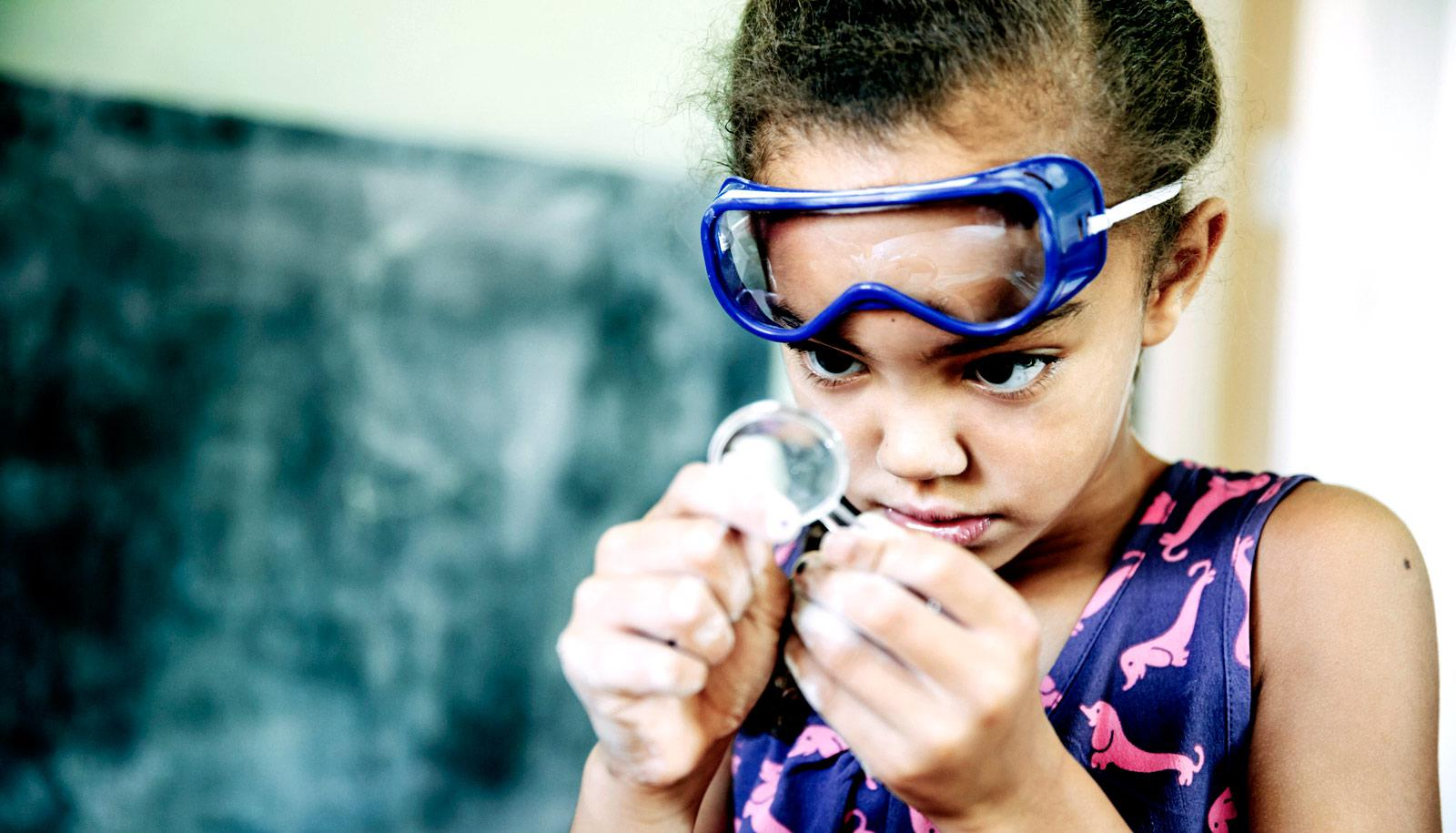 girl in goggles uses magnifying glass