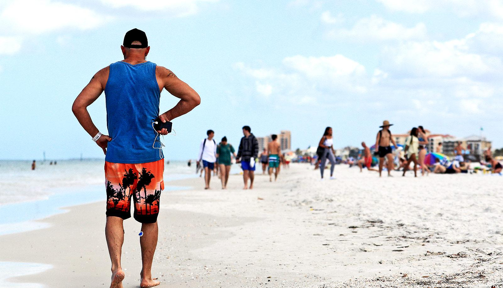 A man walks down a crowded Florida beach, packed with spring breakers