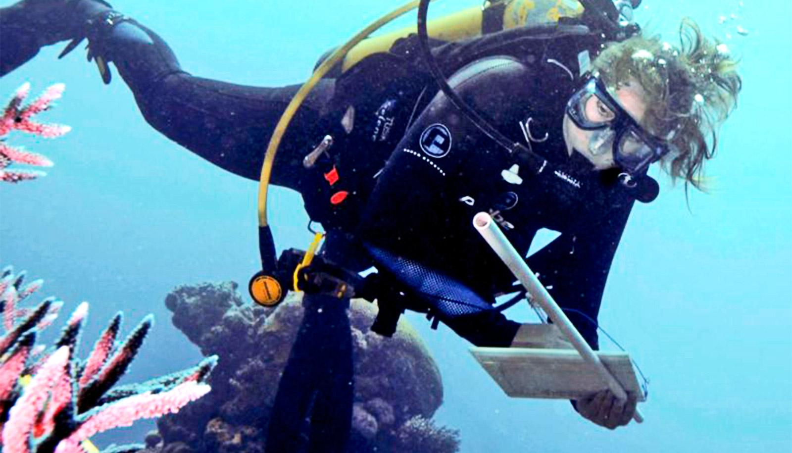 The image shows researcher Joleah Lamb diving in scuba gear to examine coral health. (corals concept)