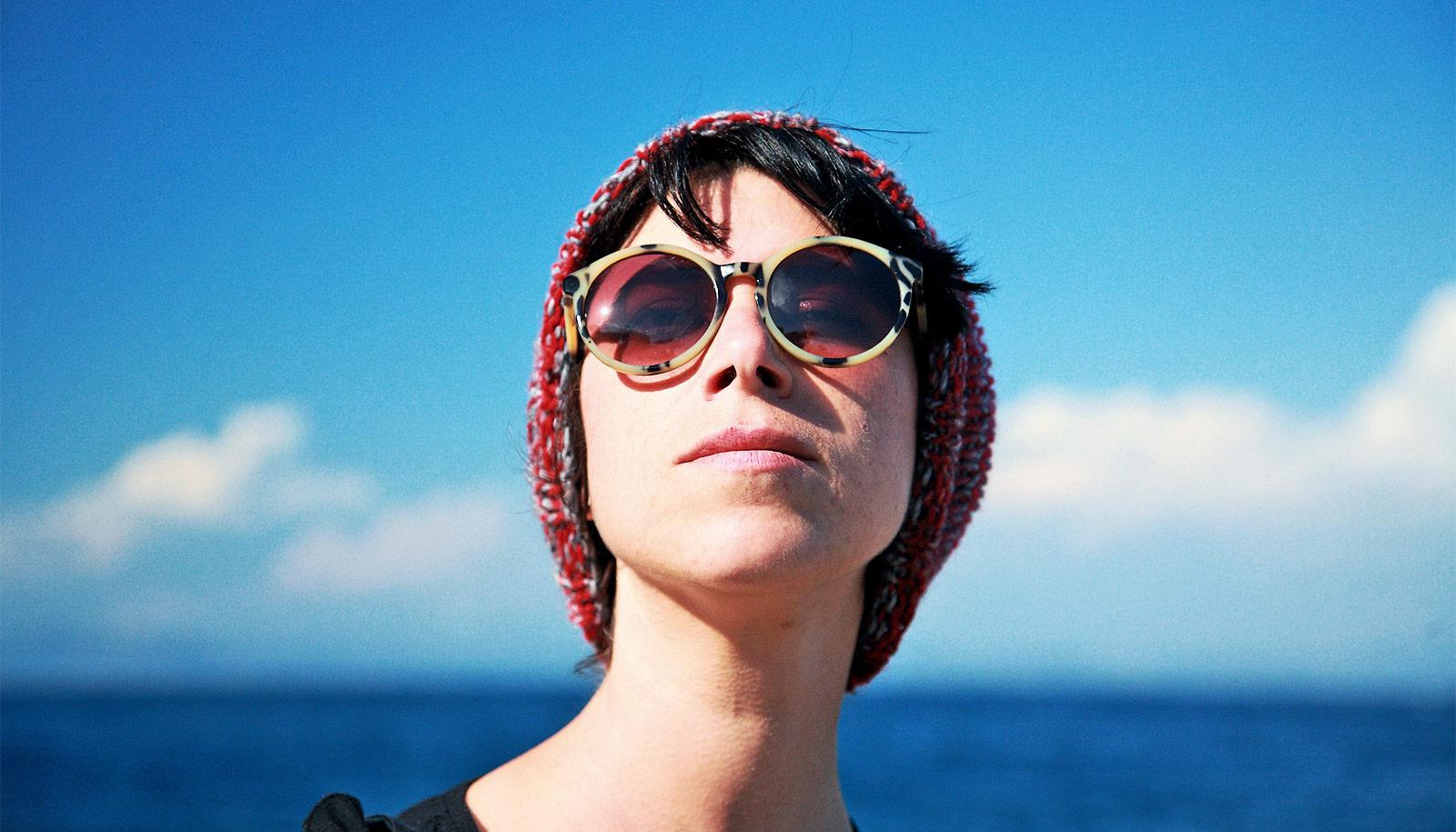 A young woman with a red beanie and red glasses stands outside looking up