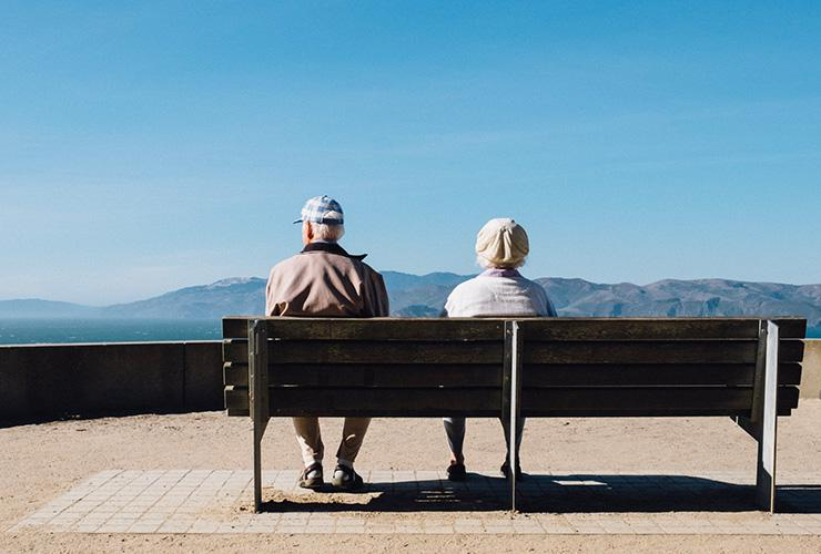 The Joy of Aging: Why and How to Embrace Getting Older by Elizabeth Torres. Photograph of an elderly couple on a bench overlooking a mountain by Matthew Bennett