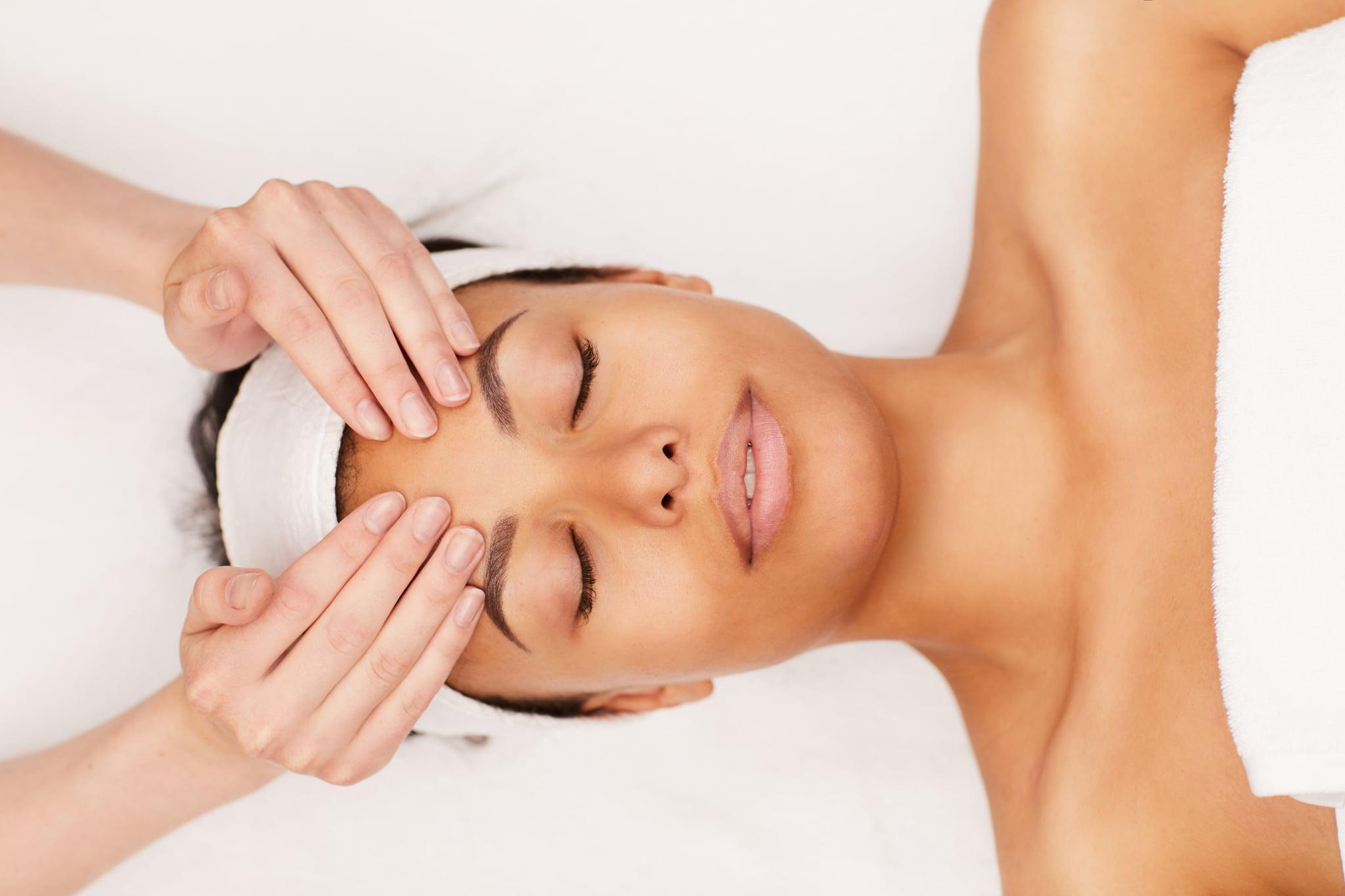 Above view portrait of beautiful mixed-race woman enjoying face massage in luxury spa, copy space