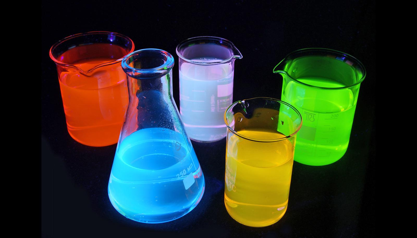 Fluorescent solutions in lab glass under UV-light.