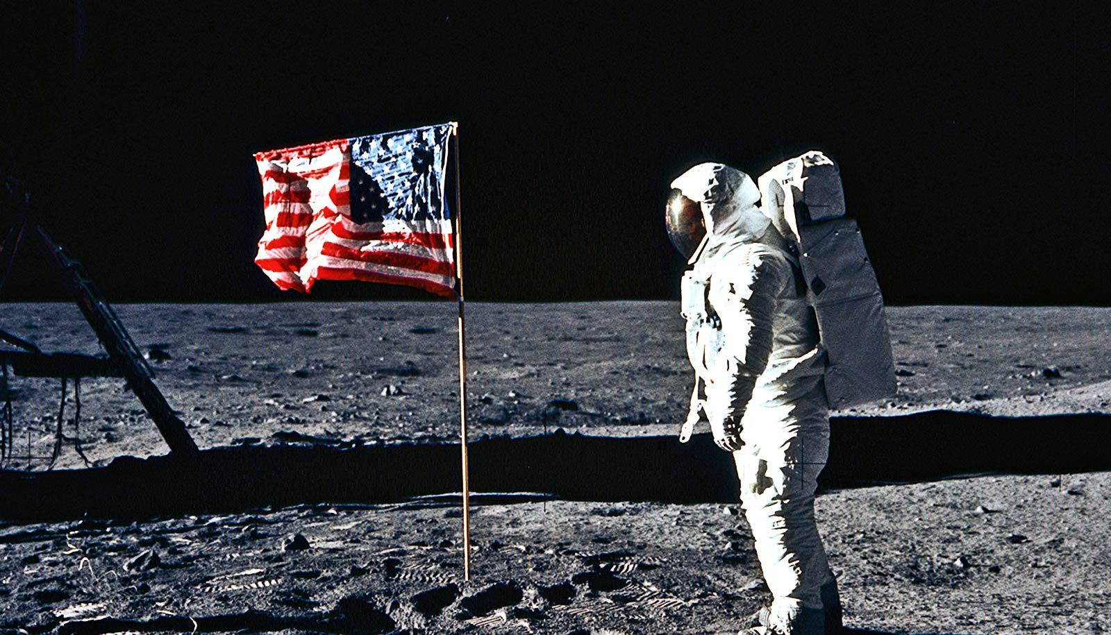 Astronaut looks at flag on the moon