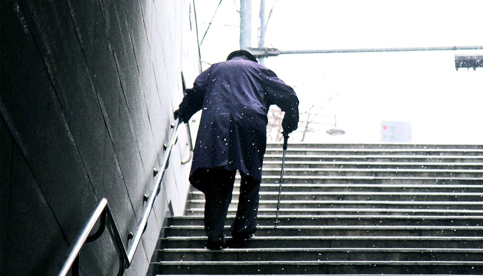 Man walking upstairs with cane (Parkinson's disease concept)