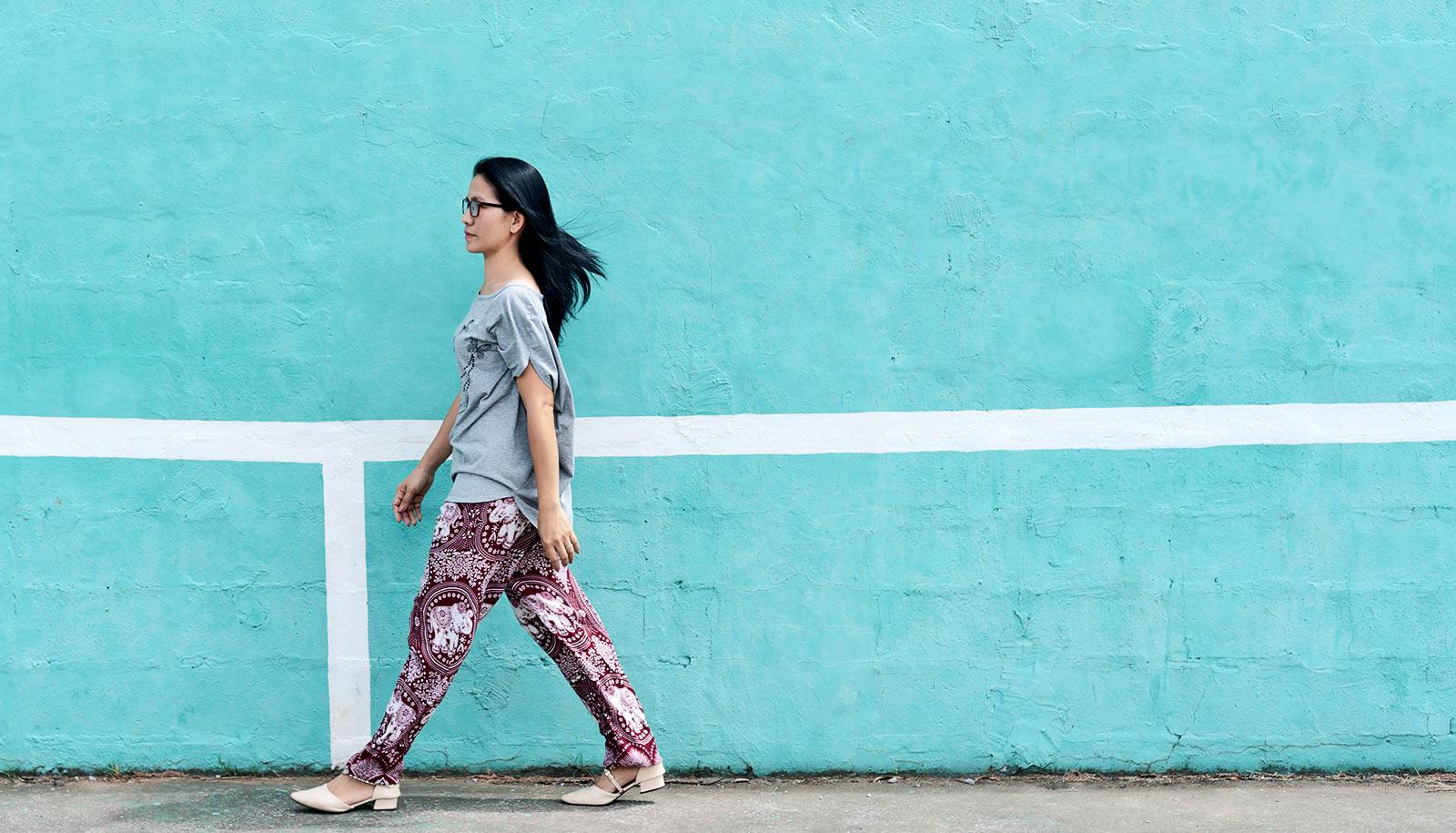 A woman in colorful pants walks against a light blue wall in profile