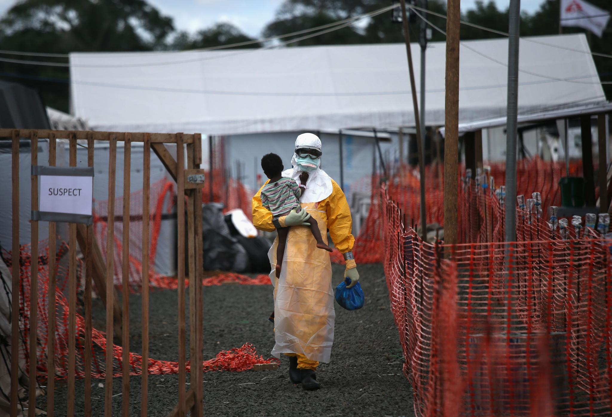 A Doctors Without Borders health worker carries a child suspected of having Ebola in October 5, 2014 in Paynesville, Liberia. A new scoring system that calculates the severity of an Ebola case could help fight outbreaks and save lives.