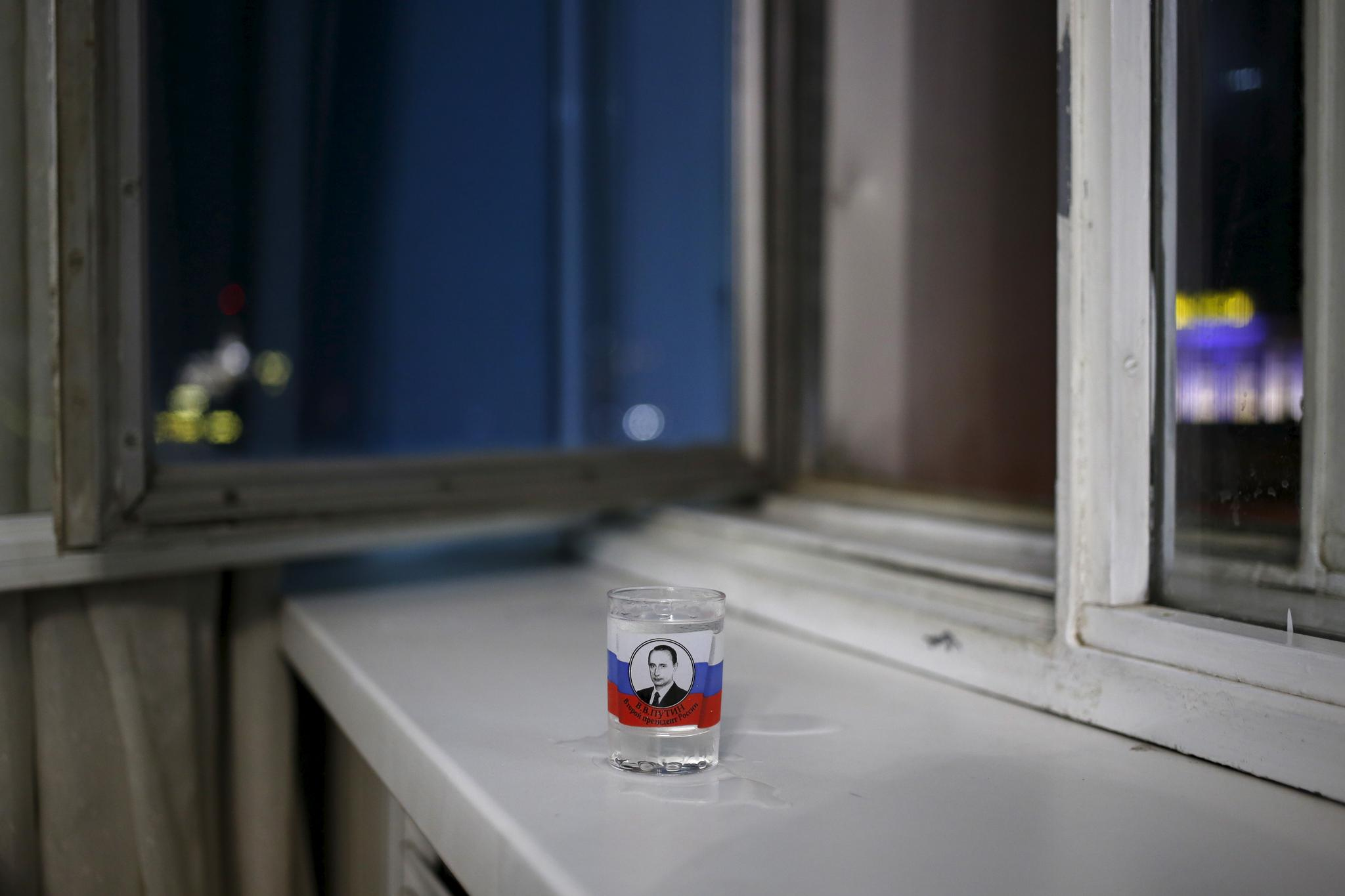 A vodka glass with a picture of Russian President Vladimir Putin sits in a hotel window in Kazan, Russia, July 31, 2015.