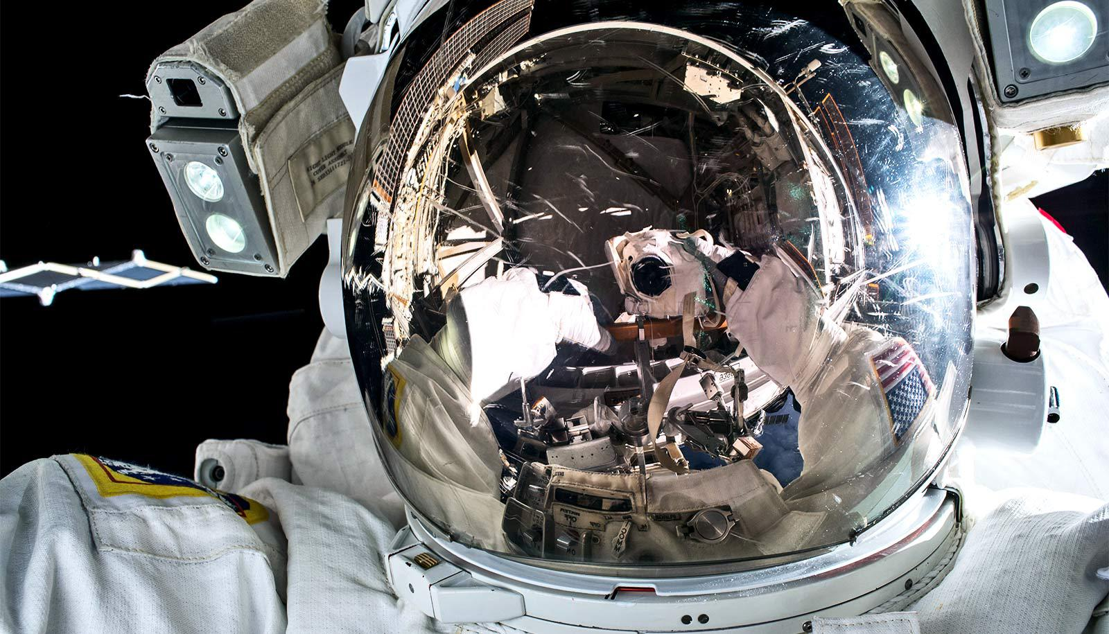 an astronaut's helmet shows the reflection of the astronaut taking a self-portrait photograph.