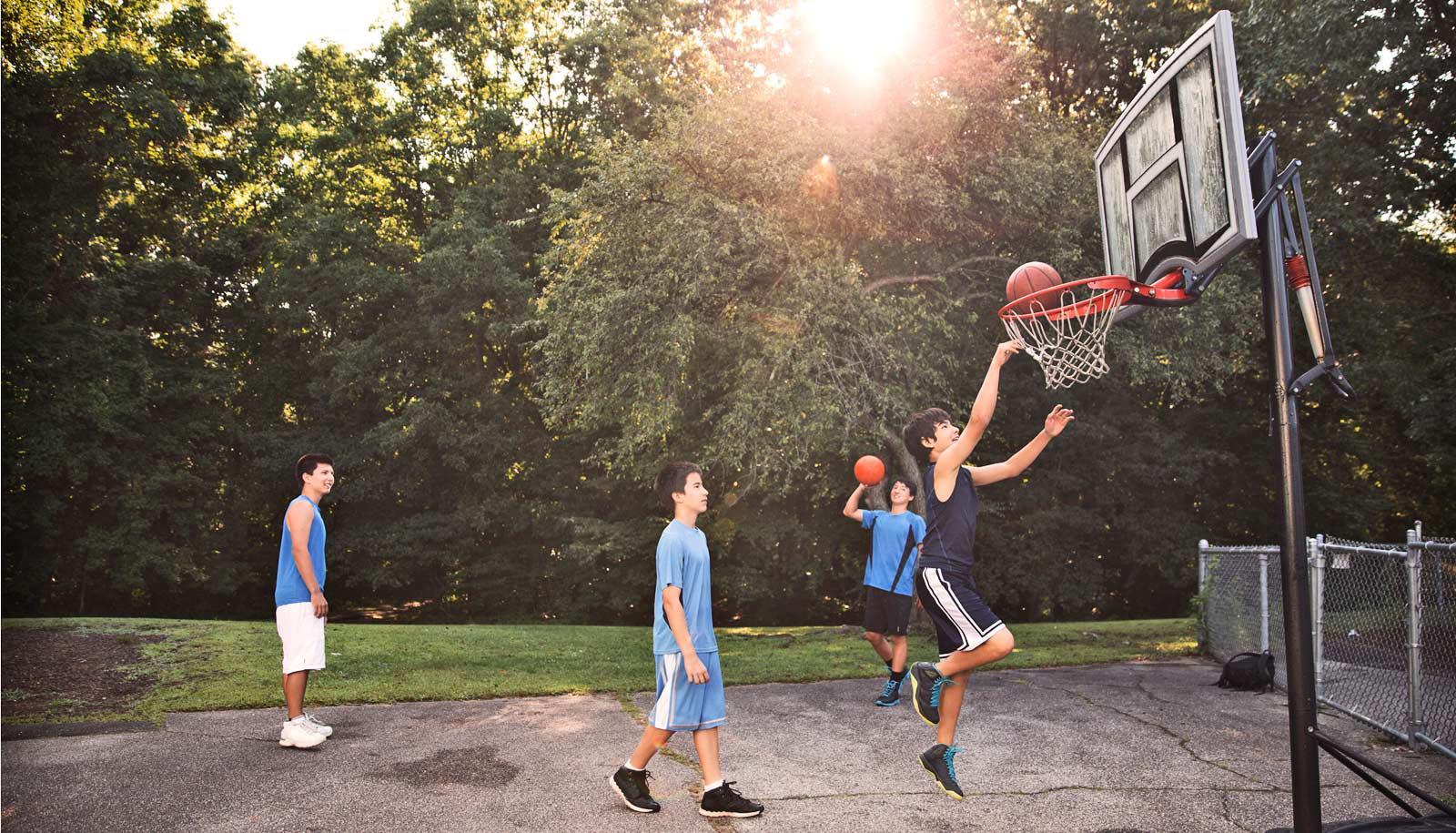 teen boys play basketball