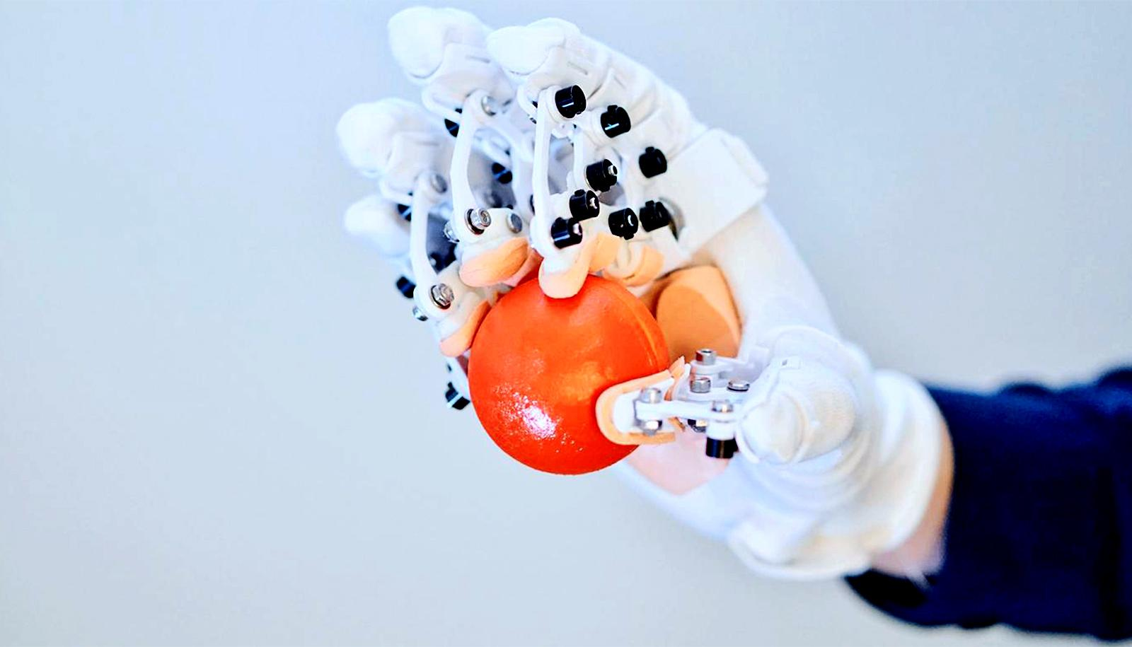 A person wearing the HandMorph glove grips a small orange ball