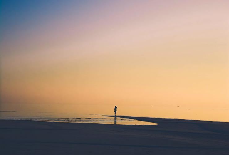 Alternative Health: Natural Stress Coping Strategies for a Calmer Life by Paisley Hansen. Photograph of a person standing at the edge of the ocean by Mishal Ibrahim