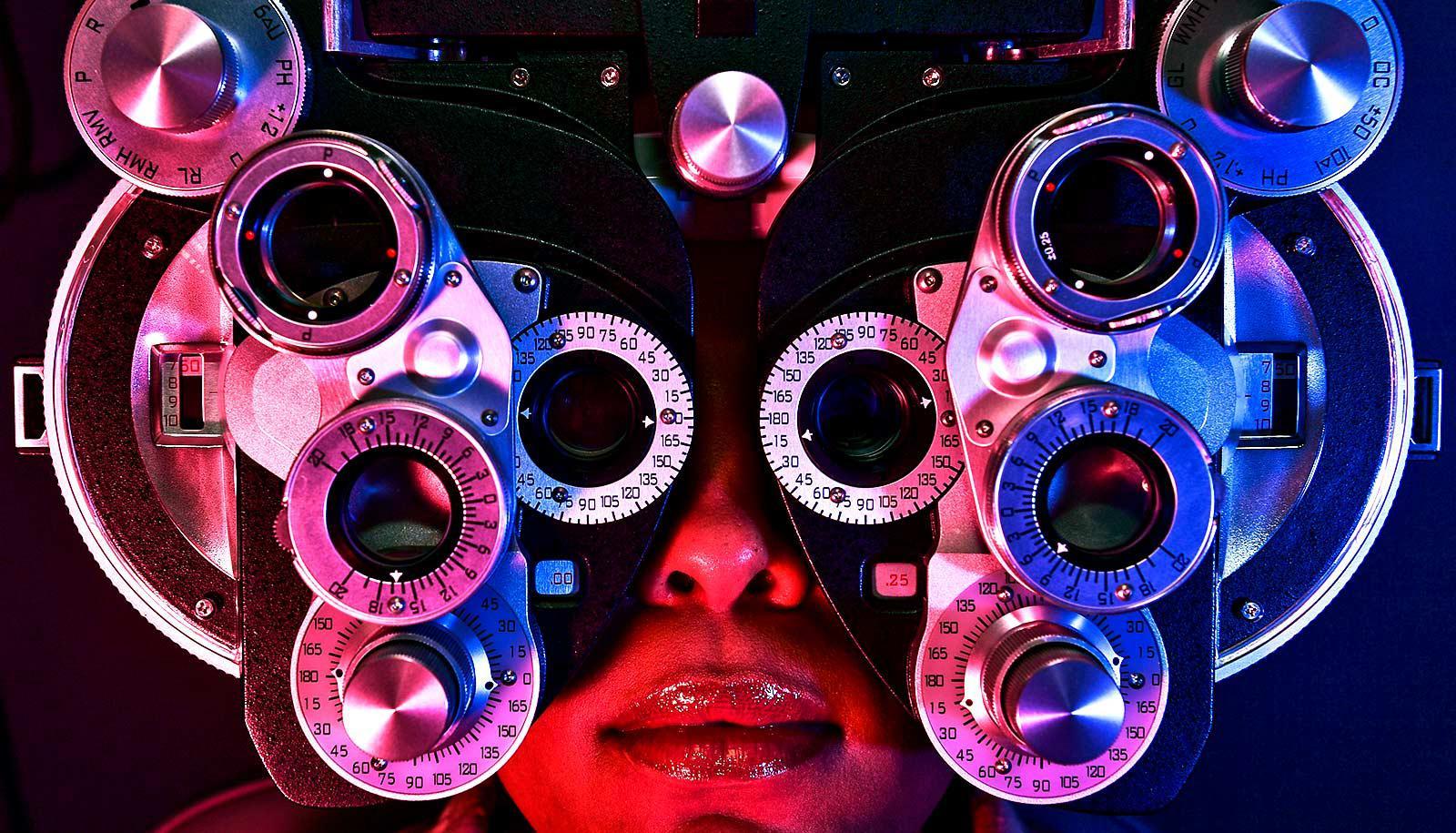 A woman looks through a vision test apparatus
