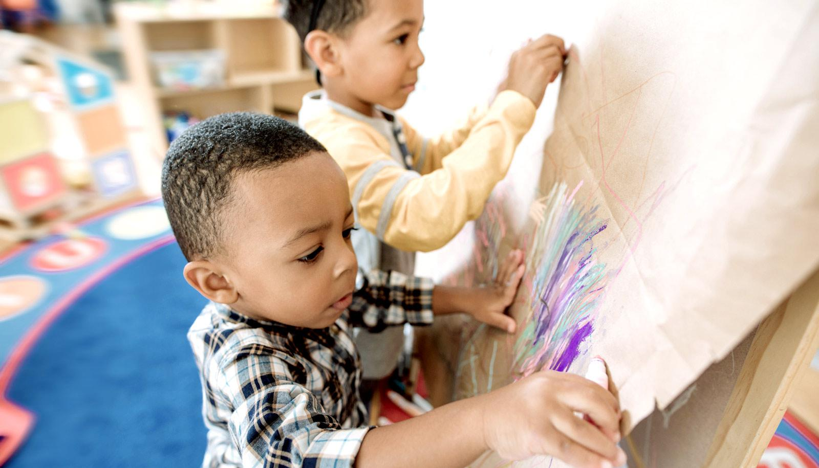 two little boys draw at easel -- early childhood education