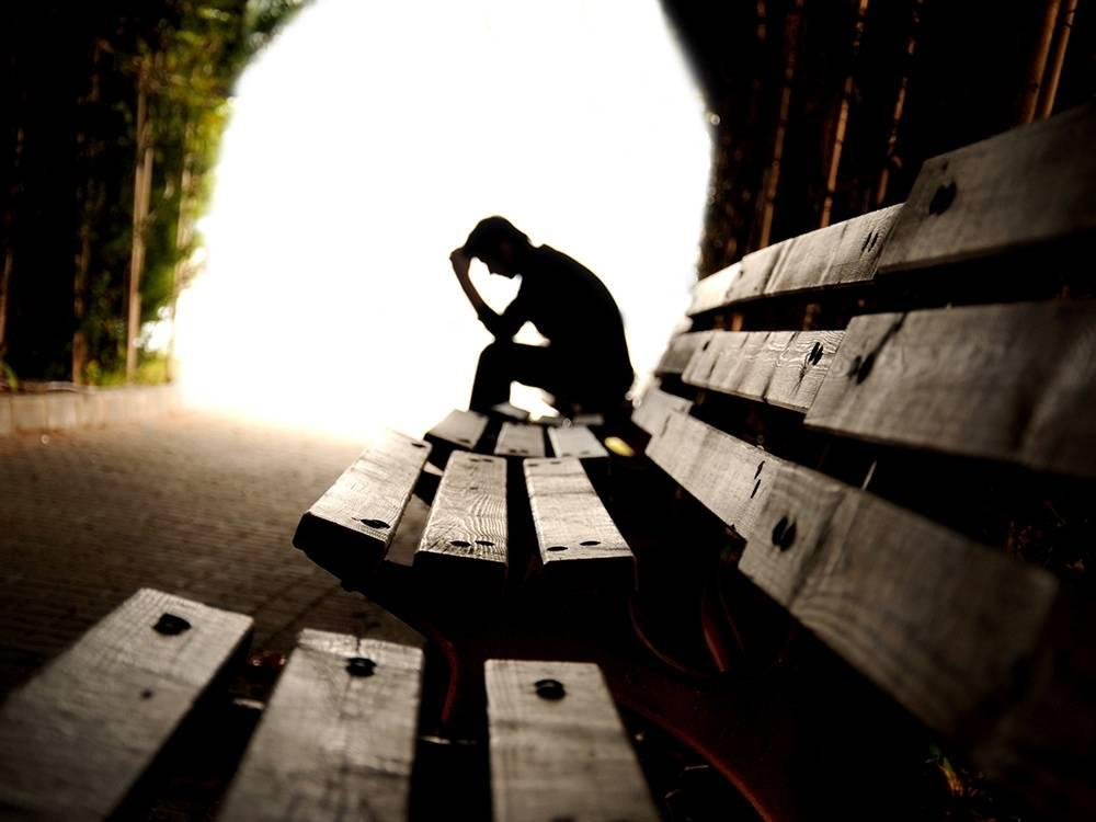 silhouetted man on bench