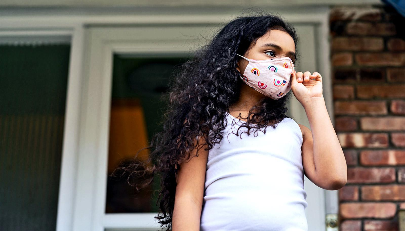 A young girl wearing a face mask stands outside her house looking up the street
