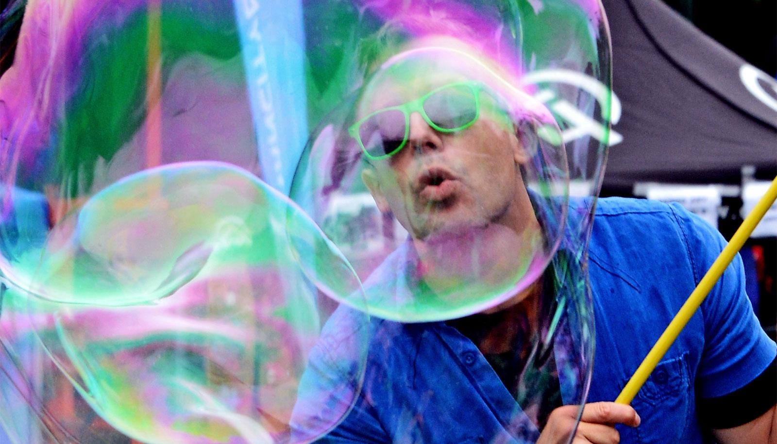 A man wearing a blue shirt and green sunglasses creating a giant soap bubble blows into the bubble