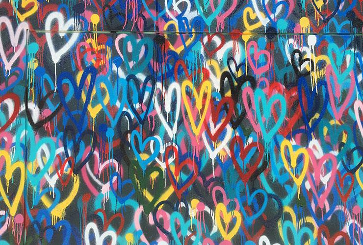 Relationship Myths: Separating from Conventions Frees Us to Enjoy Our Partners Fully by Simone Milasas. Photograph of multicolored hearts spray painted on a wall by Renee Fisher