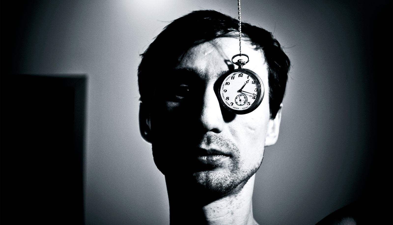 A man's face is half-covered in shadow as a pocket watch hangs down over his left eye