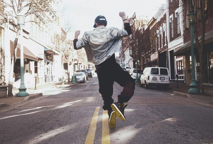Flipping your Mindset: The Healing Power of Affirmations, Mindfulness and Gratitude by Daniel Wittler. Photograph of a man skipping through the city by Andrew Hunter