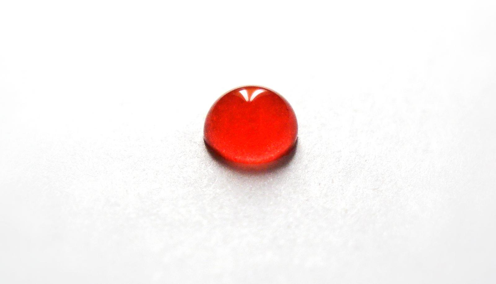 A drop of blood sits on a white surface