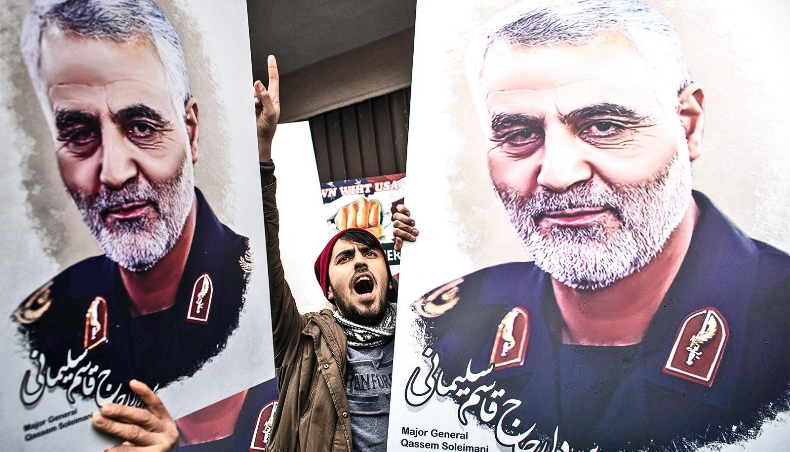 Protestors hold up Soleimani's portrait on large posterboards, with one young man raising his hand and shouting