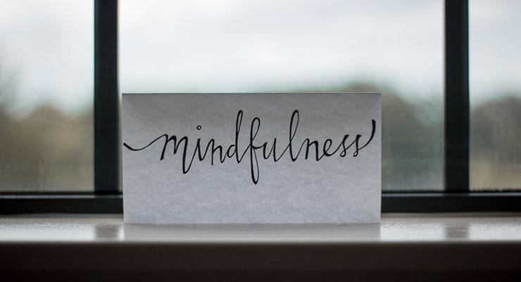 "Life After Addiction: How Mindfulness Improved My Way of Life by Cassidy Webb. Photograph of a note card that reads ""mindfulness"" placed on a window by Lesly Juarez"