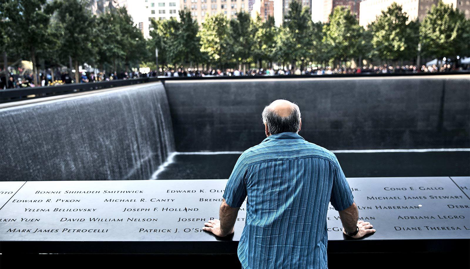 man at 9/11 memorial (trauma concept)