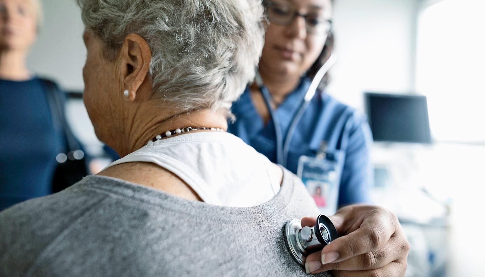 medical worker holds stethoscope on woman's back