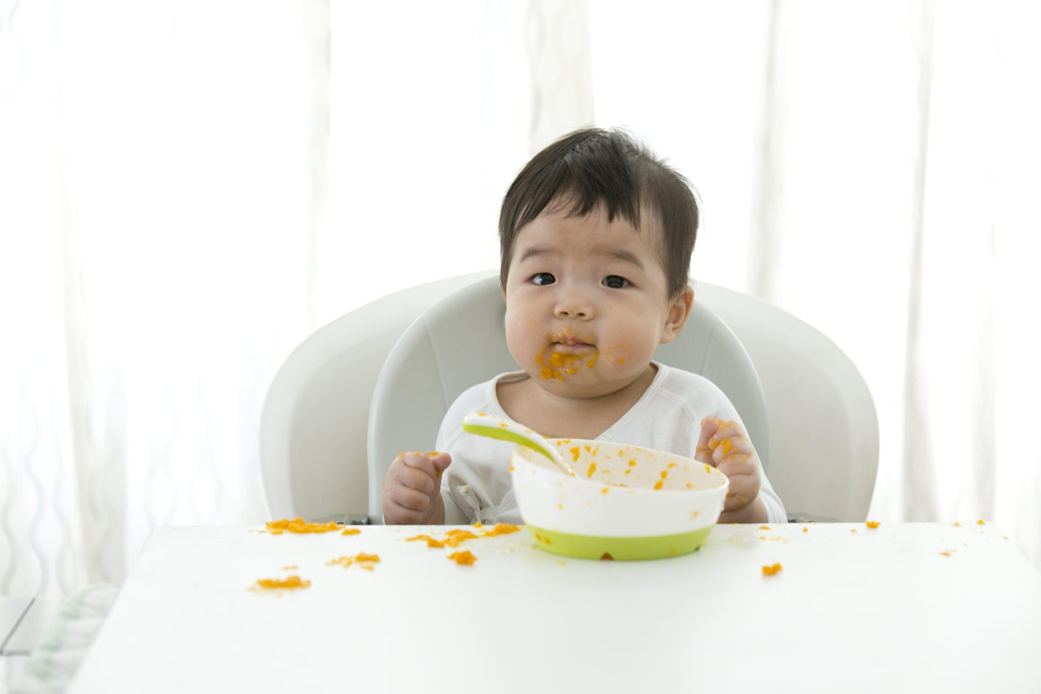 Asian baby learning self feeding on white background.