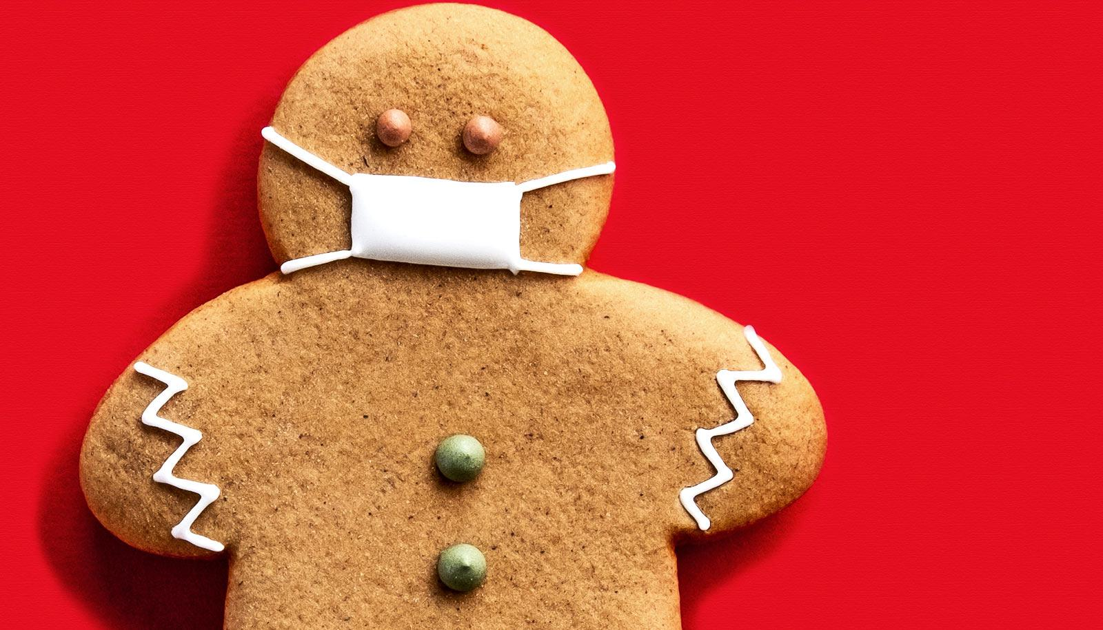 A gingerbread cookie person wears a medical mask made of frosting