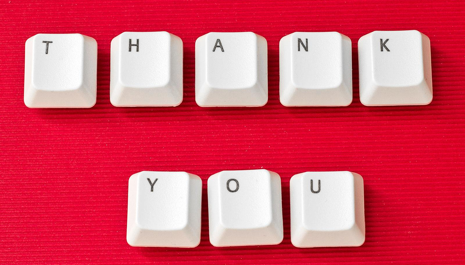 "Computer keys spell out ""Thank You"" on a red background"