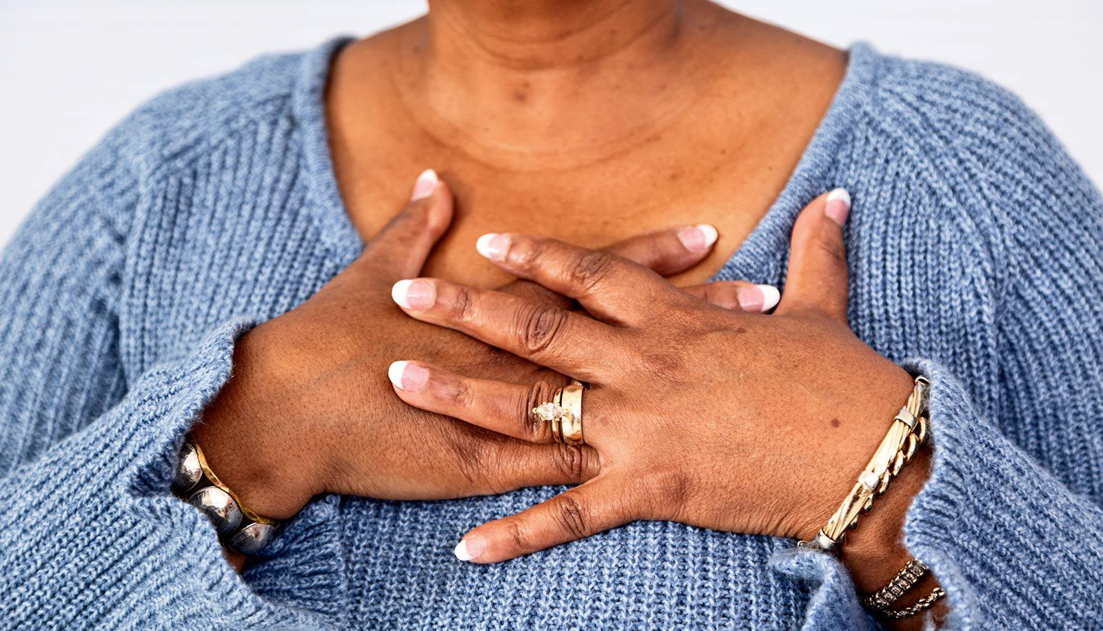 older woman lays hands on chest