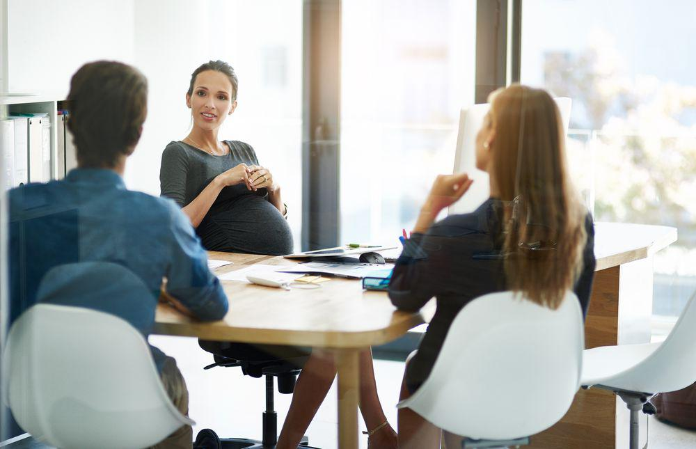Pregnant Woman at Desk with Colleagues