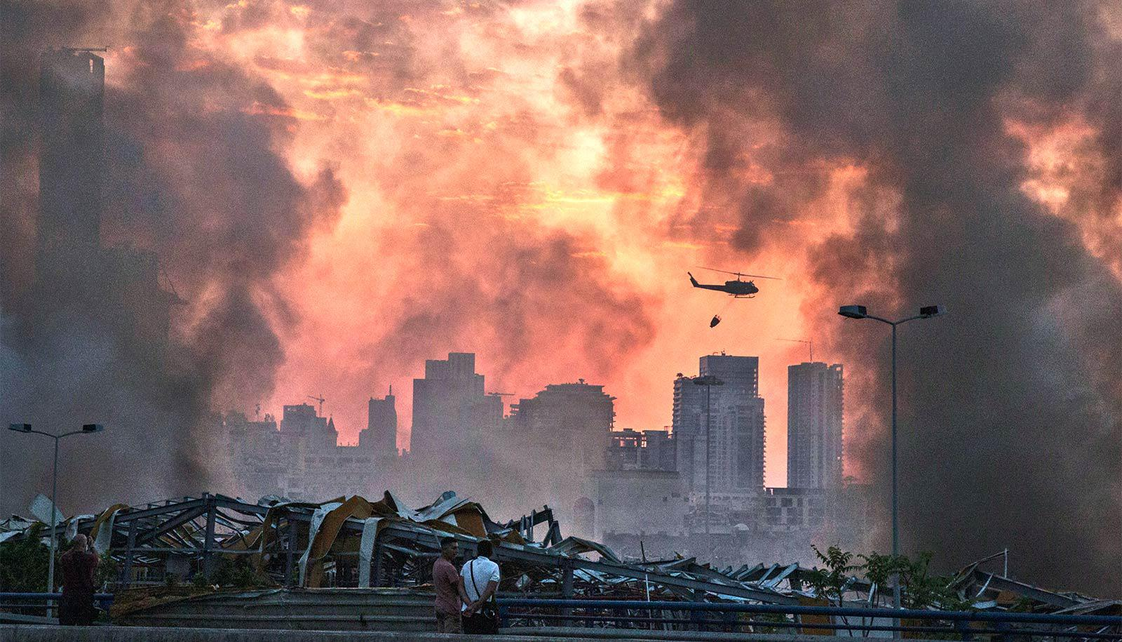 Helicopters fly over the site of the explosion as people look over wreckage and smoke billows into an orange sky