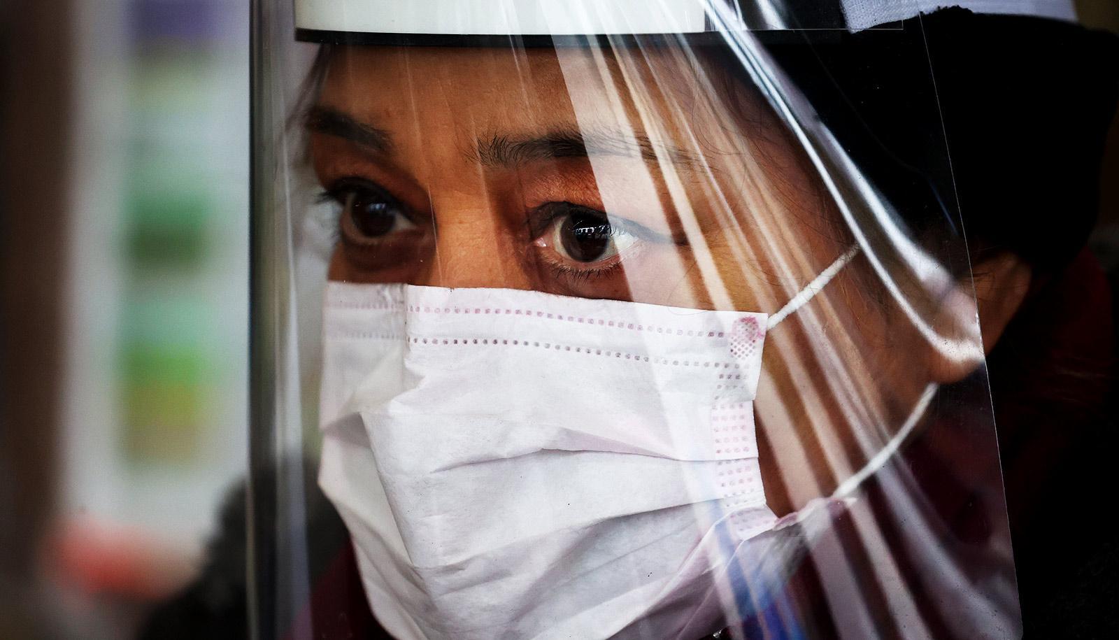 woman wears mask, face shield