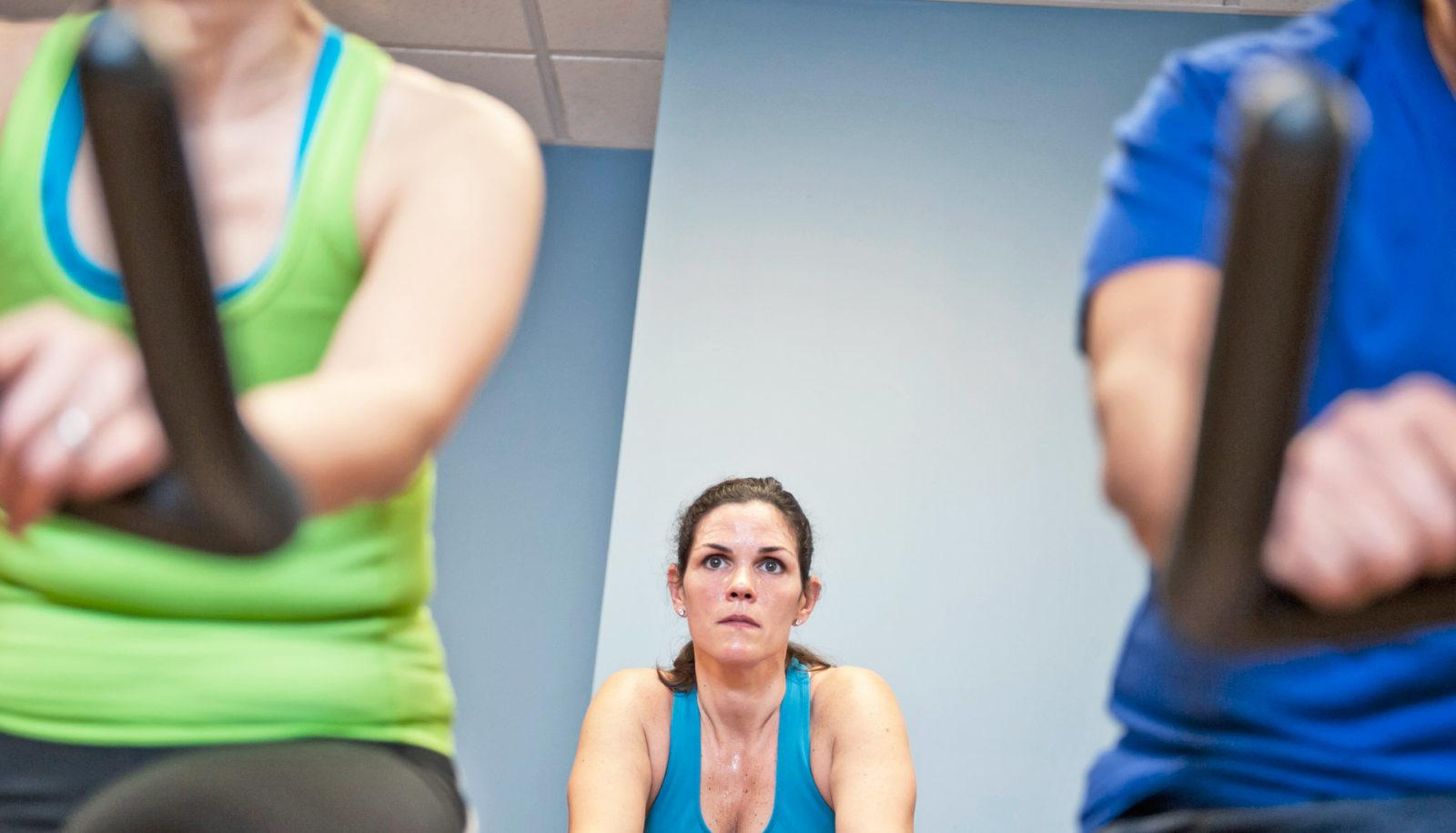 woman between two other people in spin class
