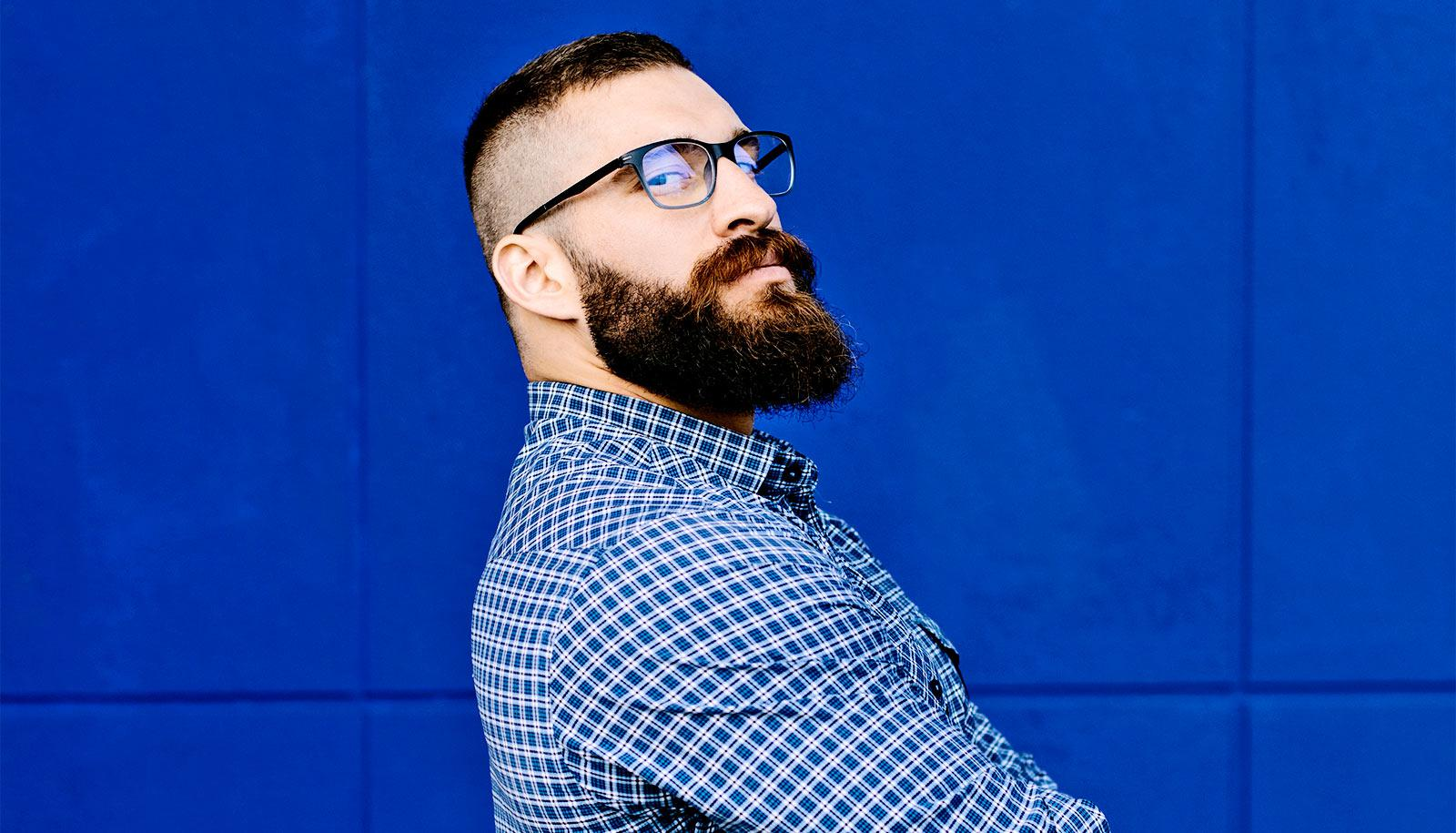 A man with a beard and glasses crosses his arms and looks over his shoulder while standing against a blue wall