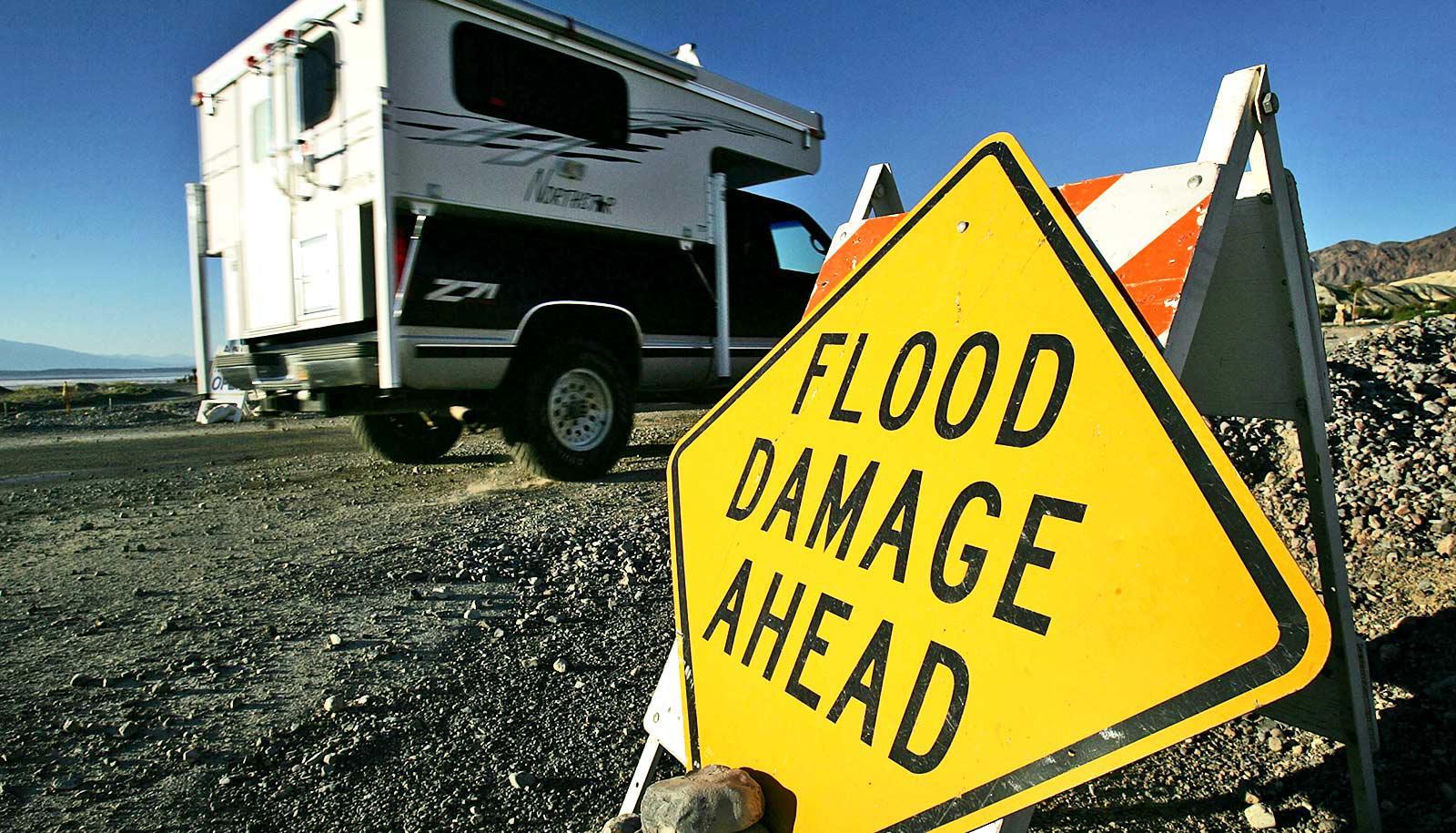 "RV drives past ""flood damage ahead"" sign on road"