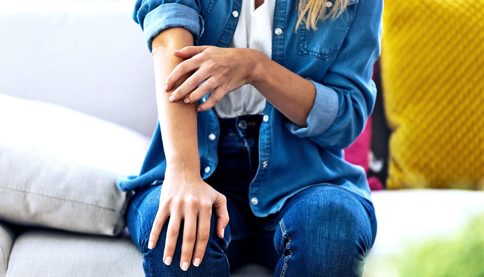 A woman touches the skin on her arm