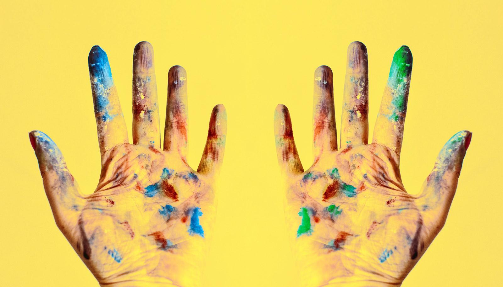two paint-covered hands on yellow
