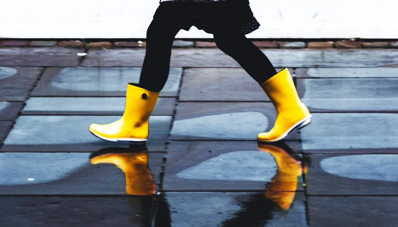 legs of person striding in yellow rain boots