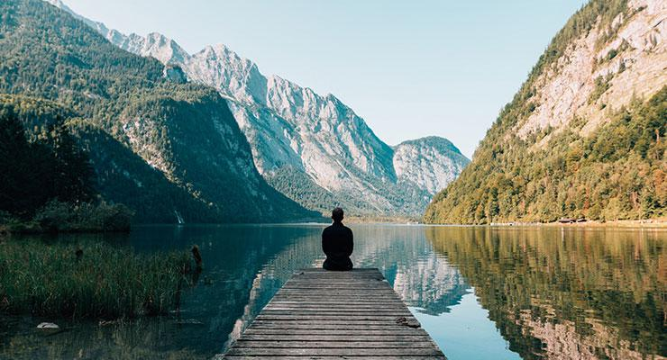 Mind Games: Exercising Your Mind for Emotional & Mental Health, by Annette Quarrier. Photograph of a man meditating in the mountains by Simon Migaj