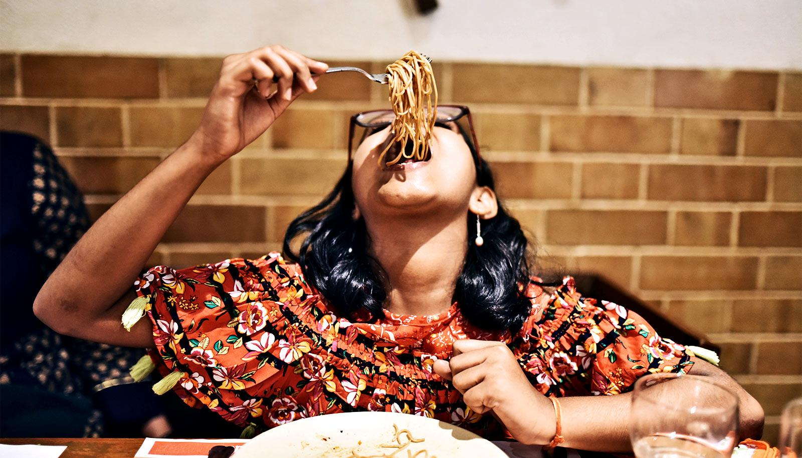 A young woman in an orange dress leans her head back to eat a huge forkful of noodles with a brick wall in the background