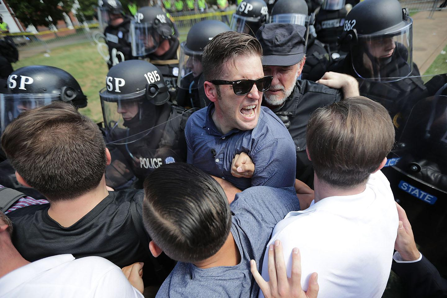 """White nationalist Richard Spencer, center, and his supporters clash with Virginia State Police in Emancipation Park after the """"Unite the Right"""" rally was declared an unlawful gathering on August 12, 2017, in Charlottesville, Virginia."""