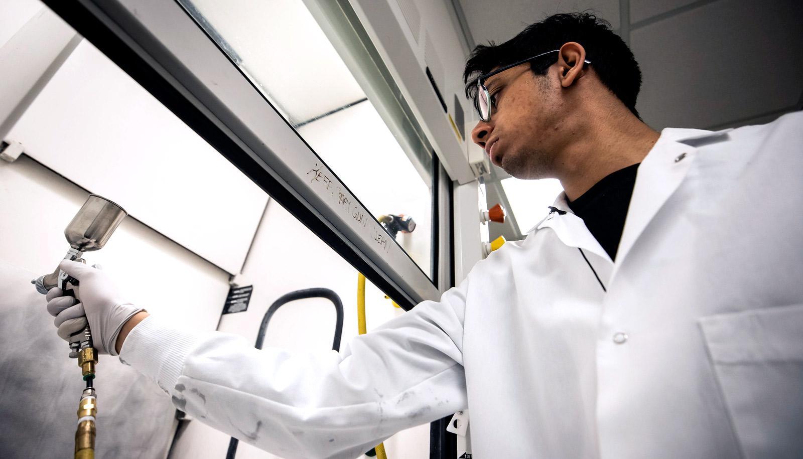 researcher in lab coat sprays coating